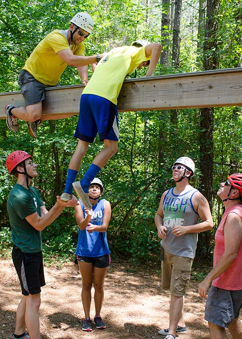 Ropes course participants doing a teamwork exercise